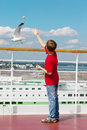 Boy feeds seagulls with pieces of bread Royalty Free Stock Images