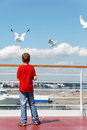 Boy feeds seagulsl on deck of ship. Royalty Free Stock Photo