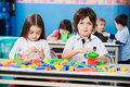 Boy with female friend playing blocks in portrait of cute little kindergarten Stock Image