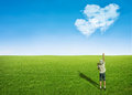 Boy field clouds in shape of heart young green grass pointing blue sky with love concept Stock Photos