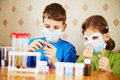 Boy fills chemical test tube specimen girl sits near to him focus boy face Royalty Free Stock Image