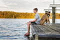 Boy fishing with dog on dock at lake side view Stock Photography