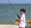 Boy fishing a little in the ocean wearing baseball cap Stock Photo