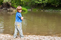 Boy fishing with rod on a river Stock Photography