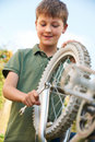 Boy fixing wheel of bike in garden Stock Photo