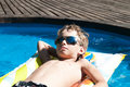 Boy floating in the swimming pool in sun glasses Stock Images