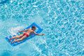 A boy floats on an inflatable colored mattress in the pool face down Royalty Free Stock Images