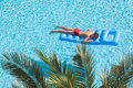 A boy floats on an inflatable mattress in the pool face down near palm leaf Royalty Free Stock Photography