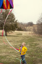 Boy flying kite laughing while wrapped up in tail streamers of Royalty Free Stock Images