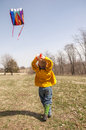 Boy flying kite working hard to keep a Royalty Free Stock Image