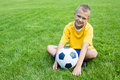 Boy football player with the ball is sitting on the football fie soccer field Royalty Free Stock Photos