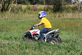 Boy four wheeling a goes in a field in the country Royalty Free Stock Image