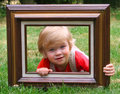 Boy in frame cute little toddler laying on a lawn looking through a wooden Stock Photos