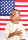 Boy in front of American flag with hand over heart Royalty Free Stock Photo