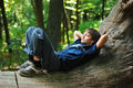 Boy with gadget in forest teenage is lying on trunk and listening to music is on his chest small earphones is his ears green is Royalty Free Stock Photo