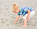 Boy gathering rocks at beach Stock Photos