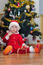 Boy with a gift under the christmas tree thinking in Stock Images