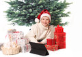 The boy with gifts sits against new year tree Royalty Free Stock Photography