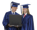 Boy and girl in blue graduation robe and cap looking at laptop over white background Stock Images