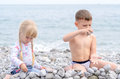 Boy and girl building stone wall on rocky beach young siblings holiday together with view of water in background Stock Image