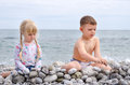 Boy and girl building stone wall on rocky beach young siblings holiday together with view of water in background Stock Photo