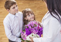 Boy and girl children give flowers as a school teacher in teache Royalty Free Stock Photo