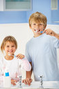 Boy and girl cleaning teeth in bathroom Stock Photos