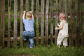 Boy and girl climbs the fence little Royalty Free Stock Photos