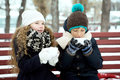 Boy with girl drink coffee together in the winter on a bench in children cup of warm cold Stock Photos