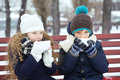 Boy with girl drink coffee together in the winter on a bench in children cup of warm cold Royalty Free Stock Photo