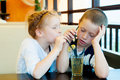 Boy and girl drink a drink through straw Stock Images