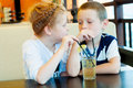 Boy and girl drink a drink through straw Stock Photos
