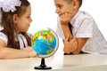 Boy and girl with globe isolated in studio in focus the kids are not in focus Royalty Free Stock Photos