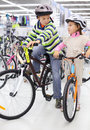 Boy and girl in helmets sit on bright bicycles Royalty Free Stock Photos