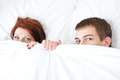 Boy and girl are hiding under the blanket Stock Photos