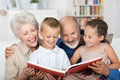 Boy and girl looking at a photo album cute sitting in the lap of their grandparents happily together Royalty Free Stock Photos