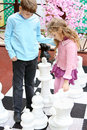Boy and girl move big chess pieces on big chessboard in park Royalty Free Stock Image