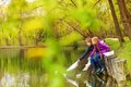 Boy and girl near the pond play with paper boats playing on water in beautiful forest landscape Royalty Free Stock Photo