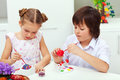 Boy and girl painting easter eggs with paintbrushes Royalty Free Stock Photo