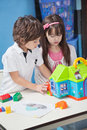 Boy and girl playing with plastic house in little at desk kindergarten Royalty Free Stock Image