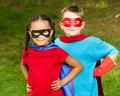 Boy and girl pretending to be superheroes pretty mixed race caucasian superhero Royalty Free Stock Photography
