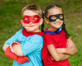 Boy and girl pretending to be superheroes pretty mixed race caucasian superhero Stock Image