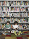 Boy and girl reading books in library full length of young Royalty Free Stock Image