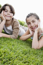Boy and girl resting chin in hands while lying on grass portrait of cute at lawn Royalty Free Stock Images