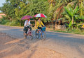 Boy girl riding bicycle umbrellas laos Stock Photo