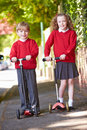 Boy and girl riding scooter on their way to school looking camera smiling Stock Photography