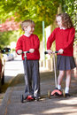 Boy and girl riding scooter on their way to school looking at each other smiling Royalty Free Stock Photos
