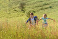 Boy and girl running on field Royalty Free Stock Photo