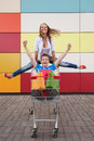 Boy and girl with shopping trolley full of purchases in the street Royalty Free Stock Photos