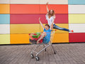 Boy and girl with shopping trolley full of purchases in the street Stock Photos